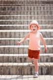 The little joyful girl went down the stairs. A child wearing a stylish hat and red shorts. royalty free stock image