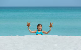 Little joyful smiling girl sitting at white sand tropical beach Stock Photography