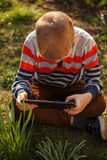 Little kid absorbed into his tablet, outdoor Stock Photos
