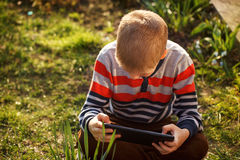 Little kid absorbed into his tablet Stock Photos