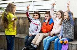 Little kid acting out phrase to friends. Happy little children acting out phrase to friends during charade outdoor Royalty Free Stock Photo