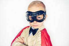 Little kid in aviator glasses and cloak. Little boy wearing aviator glasses and red cloak looking confidently at camera on studio background Royalty Free Stock Image