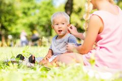 Little kid being fed by a sister. Older sister. Little sweet kid sitting on the grass while being fed by a sister royalty free stock images