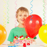 Little kid with birthday cake and balloons Royalty Free Stock Images