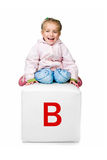 Little kid on the block with letter Royalty Free Stock Photos