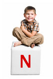 Little kid on the block with letter Royalty Free Stock Image