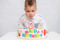 Little kid blows a candle on the cake on his birthday. A little child blows a candle on a cake on his birthday Royalty Free Stock Image