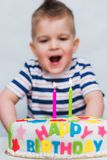 Little kid blows a candle on the cake on his birthday. A little child blows a candle on a cake on his birthday Stock Images