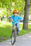 Little kid in blue jacket is cycling Royalty Free Stock Photography