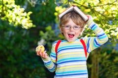 Little kid boy with apple on way to school Stock Photos