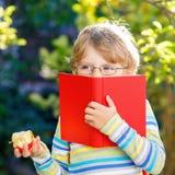 Little kid boy with apple on way to school Stock Photo