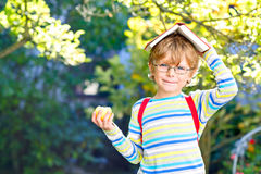 Little kid boy with apple on way to school Stock Photo