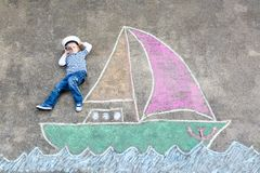Little kid boy as pirate on ship or sailingboat picture painting with colorful chalks on asphalt. Creative leisure for children outdoors in summer. Child with stock image