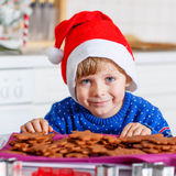 Little kid boy baking Christmas cookies at home Stock Photos