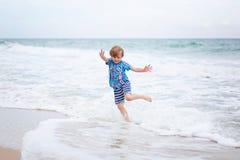 Little kid boy on the beach of ocean Stock Image