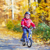 Little kid boy with bicycle in autumn forest Stock Photos