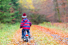 Little kid boy with bicycle in autumn forest Royalty Free Stock Photos