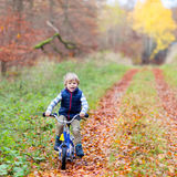 Little kid boy with bicycle in autumn forest Stock Images