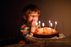 Little kid boy blowing candles on birthday cake Royalty Free Stock Images
