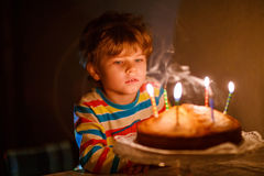 Little kid boy blowing candles on birthday cake Royalty Free Stock Image