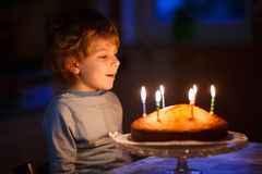 Little kid boy blowing candles on birthday cake Royalty Free Stock Photos