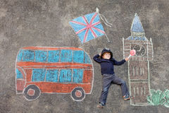 Little kid boy in british policeman uniform with London picture. Happy little kid boy in british policeman uniform having fun with London picture drawing with Royalty Free Stock Photography