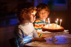 Little kid boy and brother blowing candles on birthday cake Stock Image
