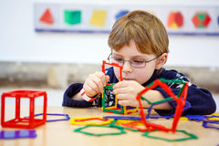Little kid boy building geometric figures with plastic blocks Royalty Free Stock Images