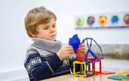 Little kid boy building geometric figures with plastic blocks Royalty Free Stock Photos