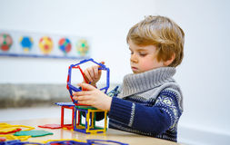 Little kid boy building geometric figures with plastic blocks Stock Photography