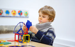 Little kid boy building geometric figures with plastic blocks Stock Photos