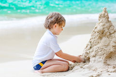 Little kid boy building sand castle on tropical beach Royalty Free Stock Image