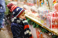 Little kid boy with candy cane stand on Christmas Royalty Free Stock Images