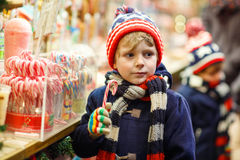 Little kid boy with candy cane stand on Christmas Royalty Free Stock Photo