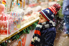 Little kid boy with candy cane stand on Christmas market Stock Photography