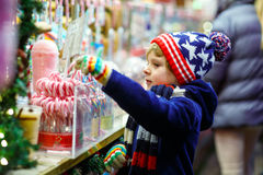 Little kid boy with candy cane stand on Christmas market Stock Photo