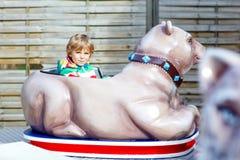 Little kid boy on carousel in amusement park Stock Images