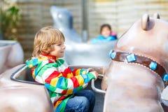 Little kid boy on carousel in amusement park Stock Photo