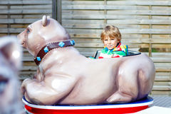 Little kid boy on carousel in amusement park Stock Photos