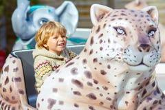Little kid boy on carousel in amusement park Stock Image