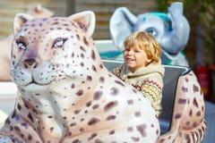 Little kid boy on carousel in amusement park Royalty Free Stock Photo