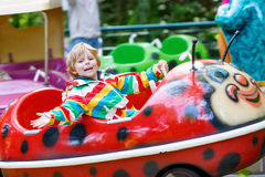 Little kid boy on carousel in amusement park Stock Photography