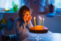 little kid boy celebrating his birthday with cake and candles Royalty Free Stock Image