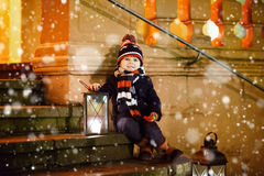 Little kid boy with Christmas lantern near church. Little cute kid boy with with a lantern near church. Happy child on Christmas market in Germany. Traditional Royalty Free Stock Images
