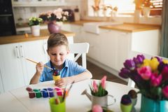 Little kid boy coloring eggs for Easter holiday in domestic kitchen. Little blond kid boy coloring eggs for Easter holiday in domestic kitchen Royalty Free Stock Images