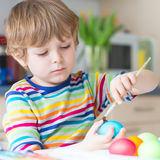Little kid boy coloring eggs for Easter holiday Stock Photos