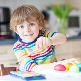 Little kid boy coloring eggs for Easter holiday Royalty Free Stock Photos