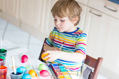 Little kid boy coloring eggs for Easter holiday Royalty Free Stock Photography