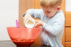 Little kid boy cooking, making cake in bowl Stock Photos