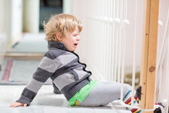 Little kid boy crying at home and showing sad mood Stock Images